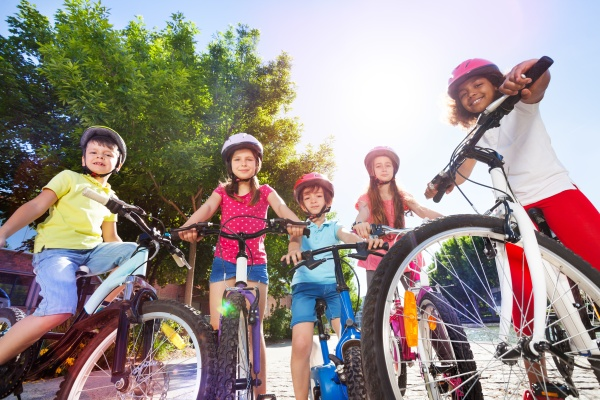 Happy children with their bicycles in summer park