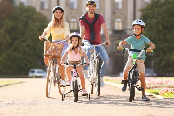 Happy family riding bicycles outdoors on summer day