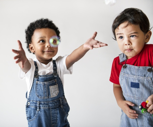 Two cute little boys enjoying playing with bubbles